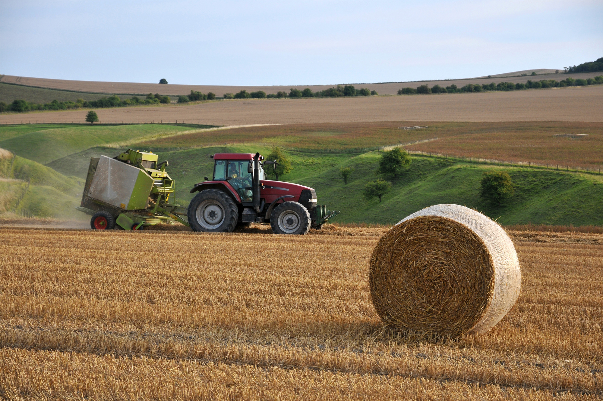 Tractor in a field behind a circular hay bale