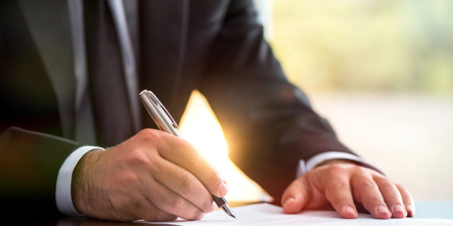 A business man writing on paper
