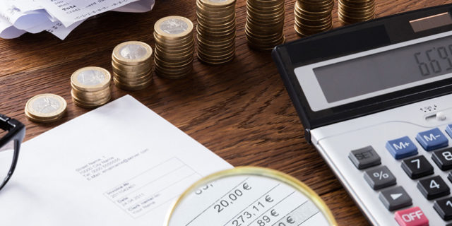 Someone calculating their finances with pound coins on the table