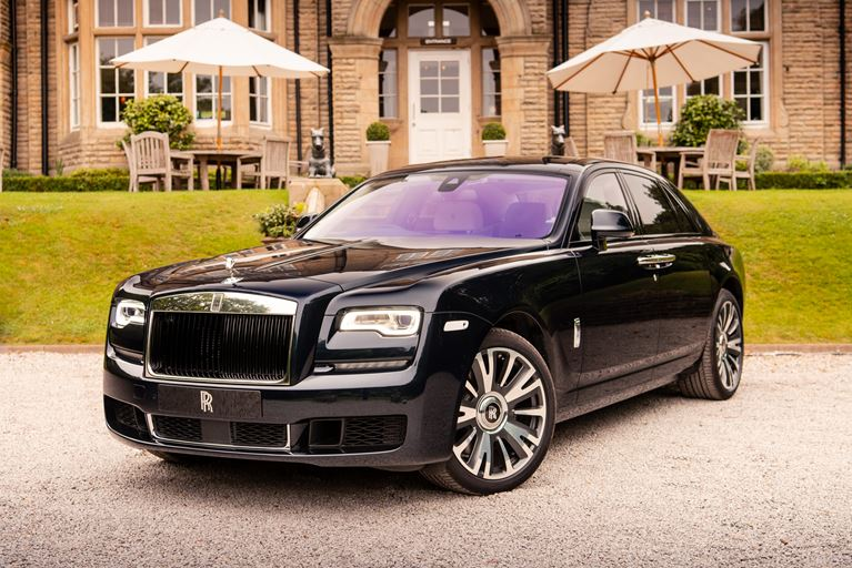 A black Rolls Royce Ghost in front of a stately home