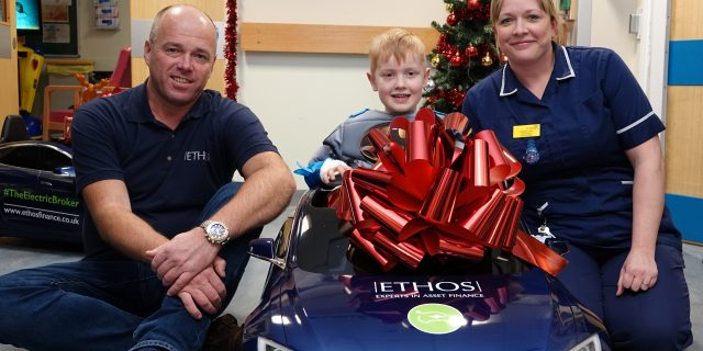 Ethos Assets Managing Director, Chris Brown with mini Tesla, child patient and nurse at Harrogate District Hospital
