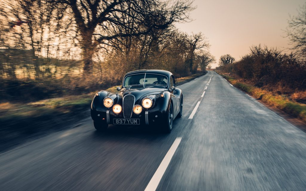 Jaguar XK120 driving down a country road