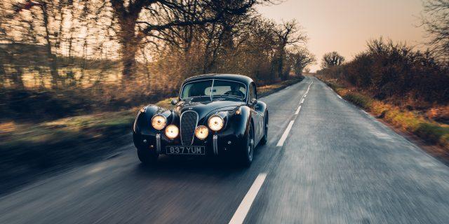 Jaguar XK120 driving down a country road