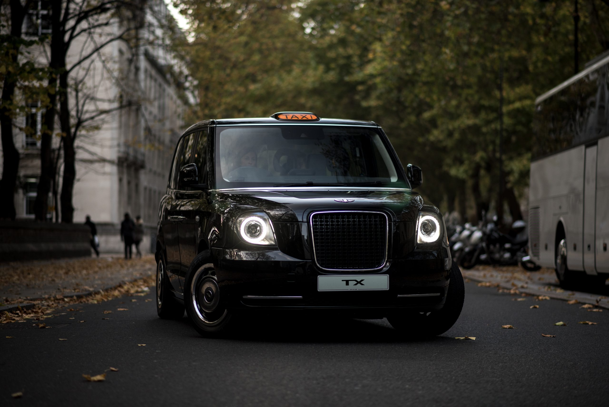 A black LEVC taxi with it's lights on