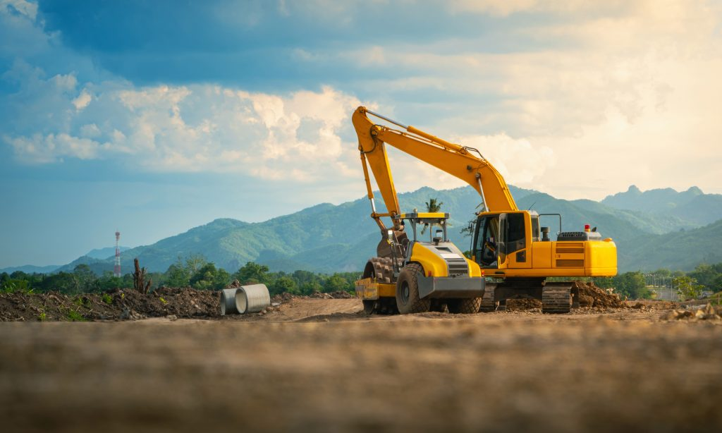 Backhoe working in road construction site, with mountains and sky background.